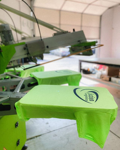 a neon green shirt with black text on it on a roq automatic press