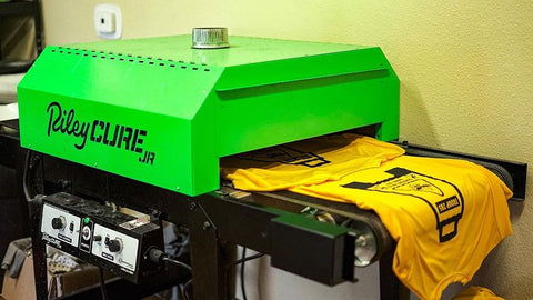 A yellow shirt with a black design on it comes out of a Riley Cure conveyor dryer