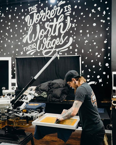 printer screen printing with a mural behind him saying the worker is worth their wages