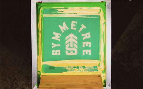 a screen on press that says symmetree with gold ink and a squeegee