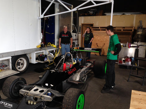 Riley Hopkins standing with his race car and two employees