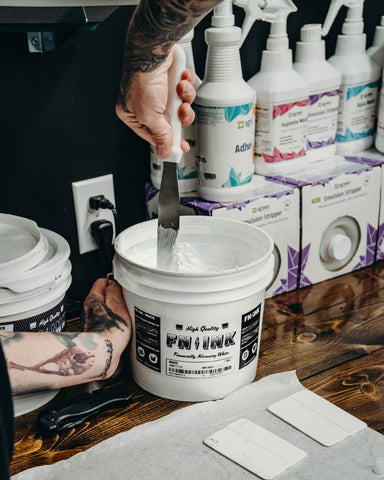 A hand stirs a bucket of white ink with a spatula