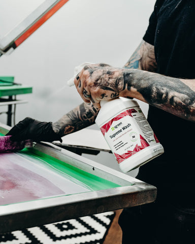 person spraying supreme wash on a screen