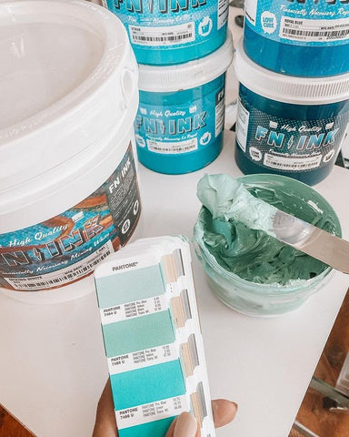 A Pantone swatch next to a bucket of mixed ink and Mixing White