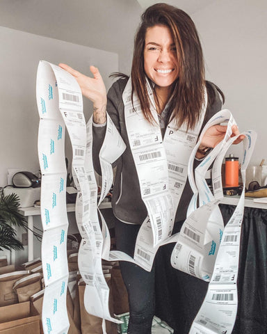 woman standing with a bunch of order stickers