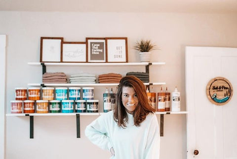 A woman poses in front of a shelf of ink