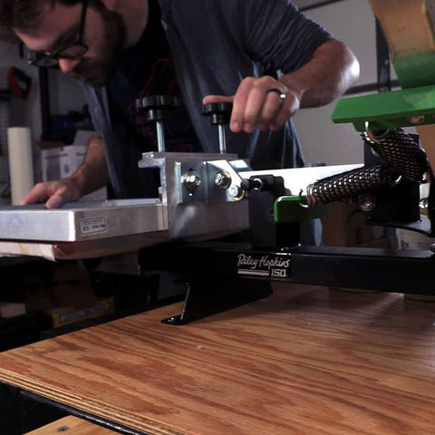 person registering a print on a riley 150 press