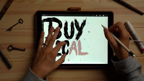 person drawing buy local on an ipad