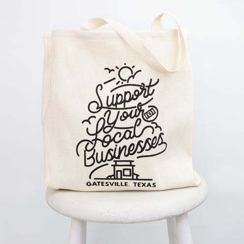 """A tote bag reading """"support local businesses, Gatesville Texas"""" sits on a white stool"""