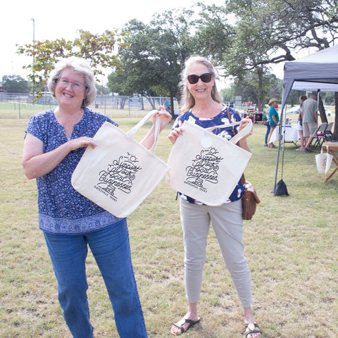 """Two women holding """"support local"""" tote bags in a field next to a vendor tent"""
