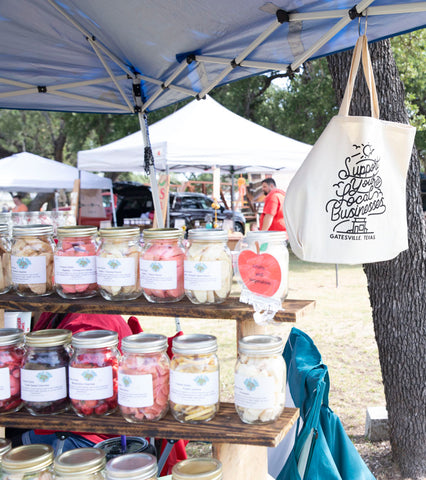 """A canvas tote bag reading """"support local businesses"""" hangs from a temporary tent next to mason jars"""