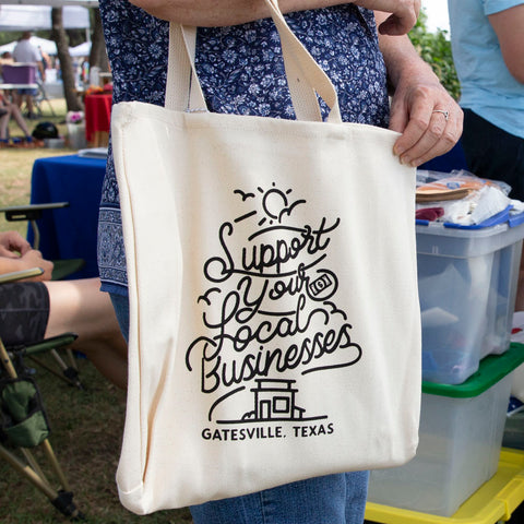 """A """"support local"""" tote bag hangs off a shopper's arm"""