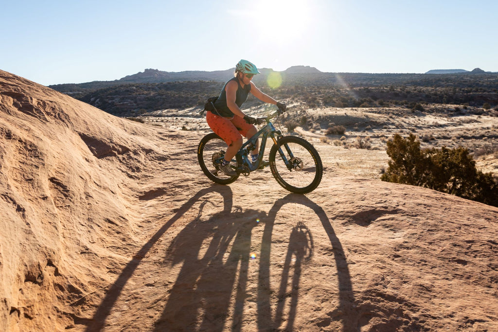 Woman riding her mountain bike over sandstone