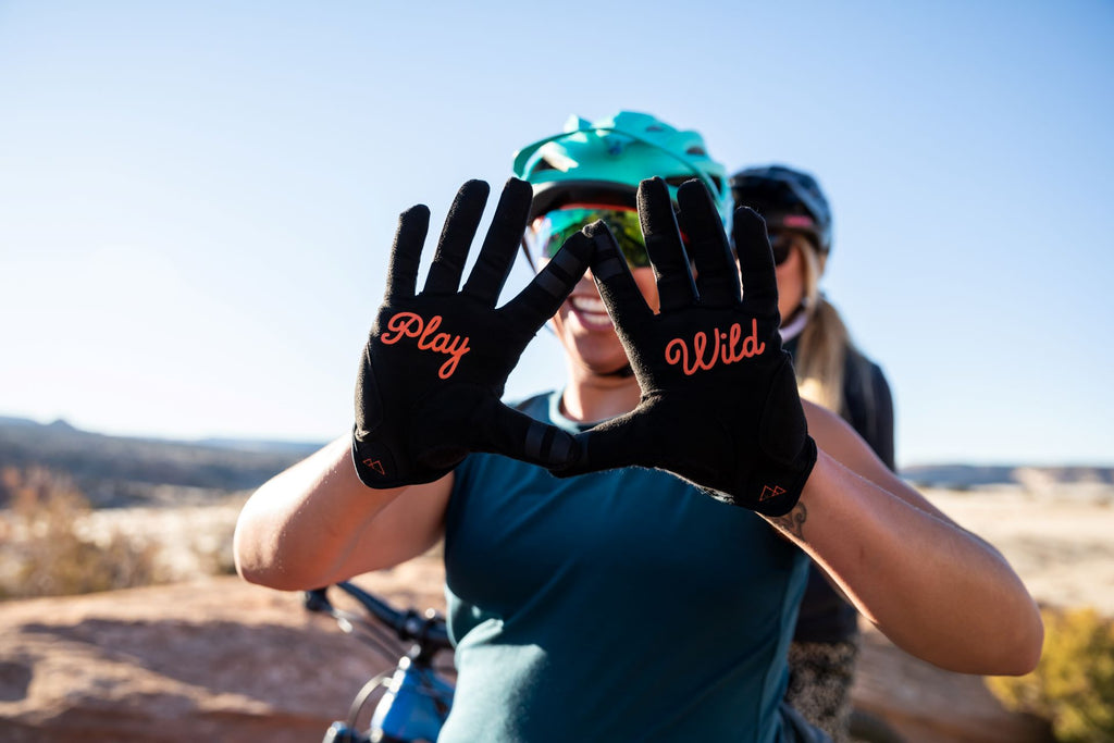 Woman holding her hands up to show you Play Wild printed on her gloves