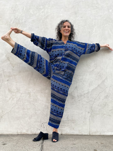 Polly Jumpsuit, Fall 2021, blue and black woven jacquard fabric used on the wrong side. Lu posing in a yoga asana with her arms outstretched and one leg in the air, utthita hasta padangutasana