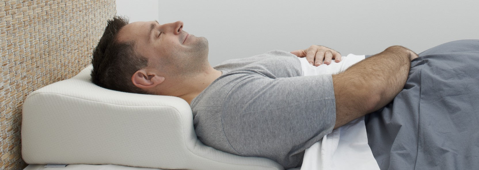 photo of man sleeping on his back on Patney sleep positioner pillow-  has an open airway