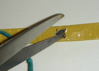 Carefully cutting a slit in one side of the quickmatch with scissors