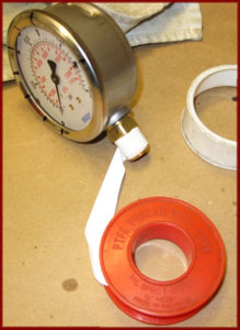 Wrapping the fitting on a pressure gauge with teflon tape