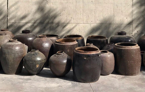Collection of antique Chinese pots positioned in front of concrete wall.