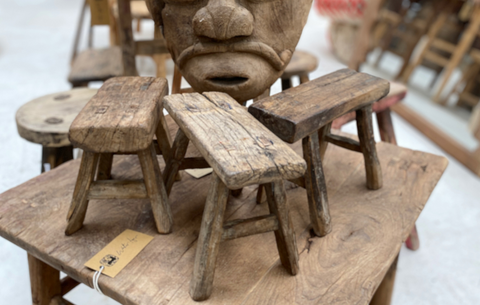 three rustic Asian furniture stools upon a table
