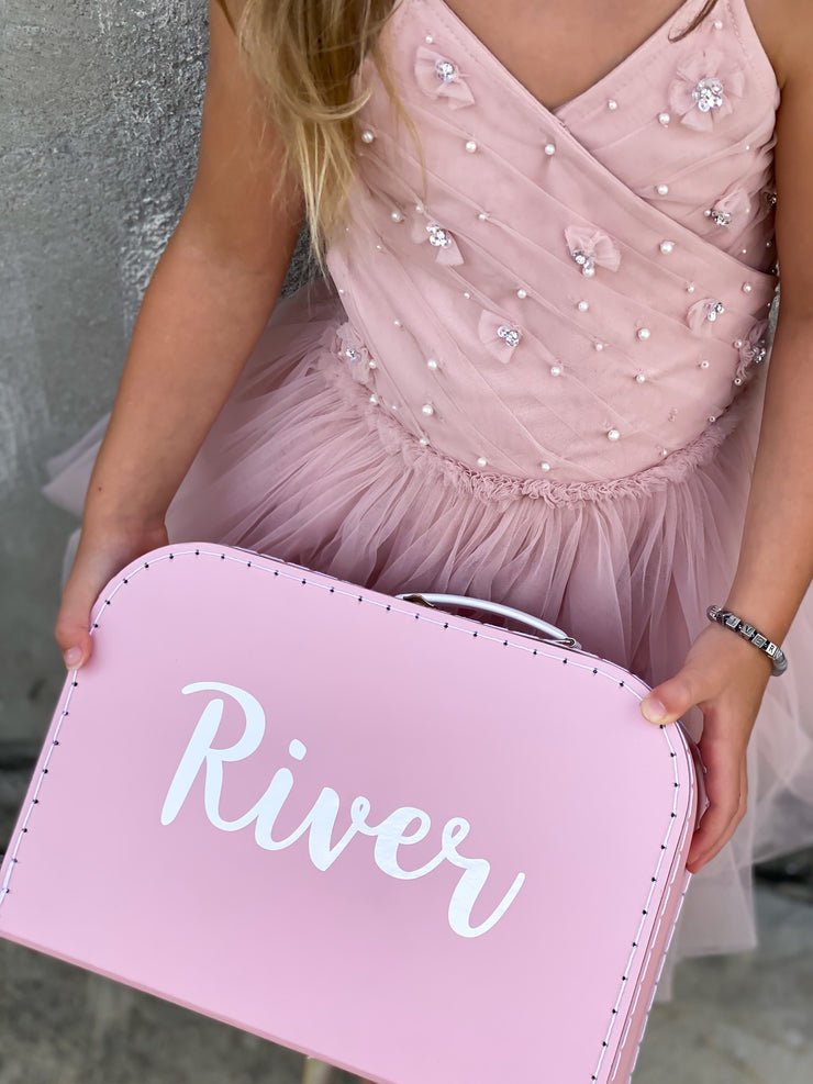 girl wearing pink tulle dress, holding a size large pink box