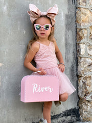 girl leaning against wall holding pink keepsake box in size large