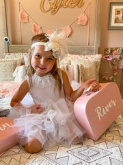 girl sitting on bed wearing white tutu, white feather headband and holding size large keepsake box
