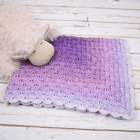 Gradient of purple to gray yarn crocheted into a lace baby blanket with a stuffed sheep.