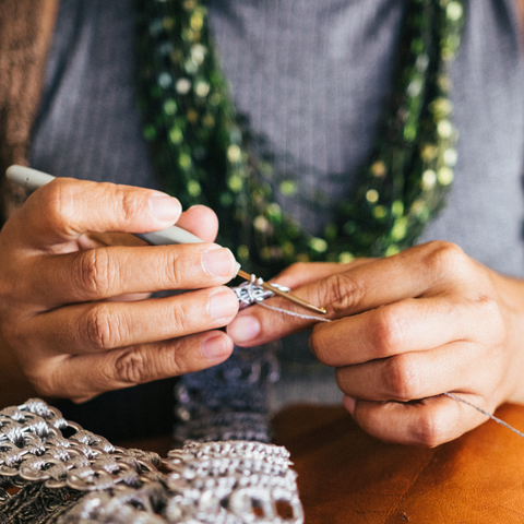 Woman crocheting with silver yarn and crochet hooks.