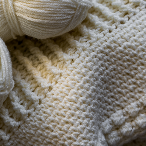 Cream skein of Plymouth Yarns Encore Worsted used to knit a beautiful throw.