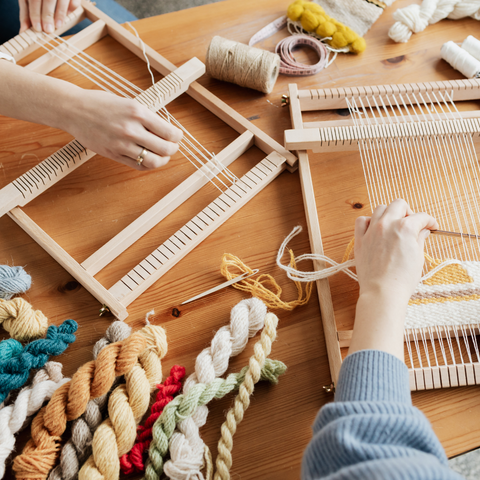 Two people weaving fibers through a weaving loom with a bunch of different colored yarn skeins next to them.