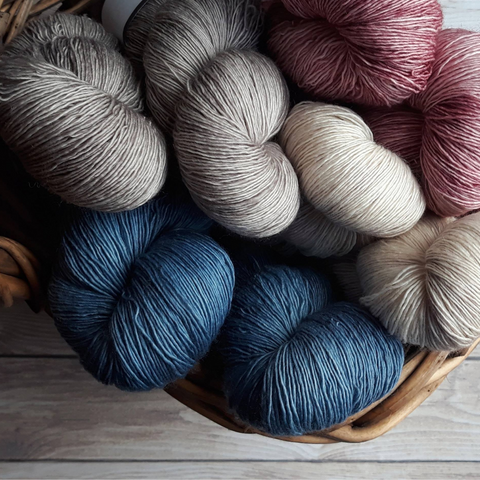 Different skeins of silver, cream, pink, and blue Malabrigo Sussuro yarns in a wooden basket.