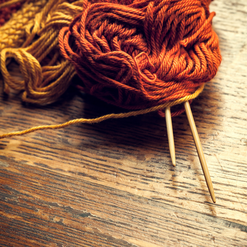 Yarn in warm gold and copper colors with wooden knitting needles on a wooden table.
