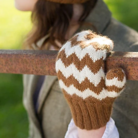 Woman wearing a hand knit gold and white chevron mitten holding on to a wooden fence rail.