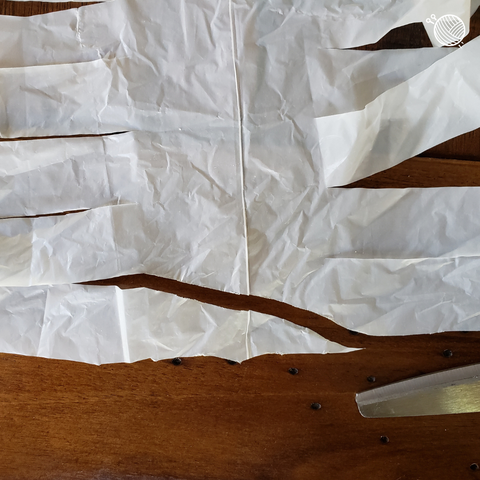 Close up of plastic bag going from strips to one long strip on a wooden table.