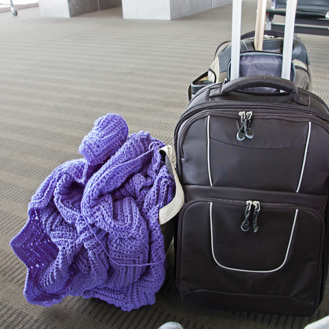 Suitcase and bag with purple crochet blanket project sitting on the floor at an airport.