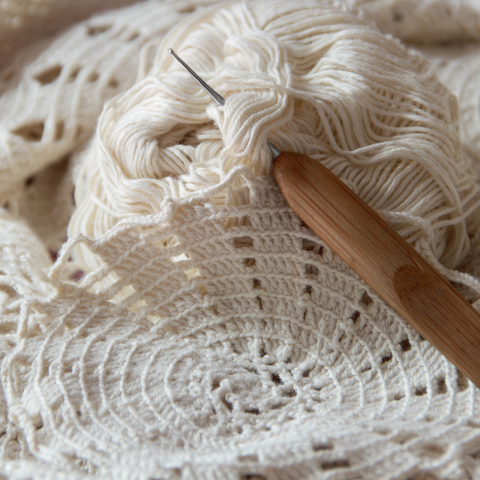 Crochet hook, cream colored yarn and the beginnings of a crochet lace project.