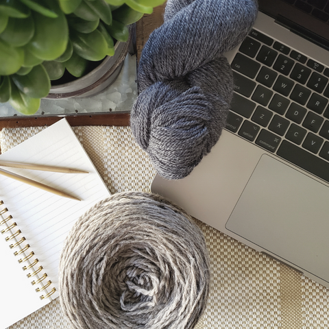 Computer open with a blue skein and naturally colored cake of yarn with notebook and knitting needles.