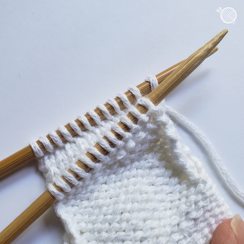 White yarn on wooden needles prepped for three-needle bind off.