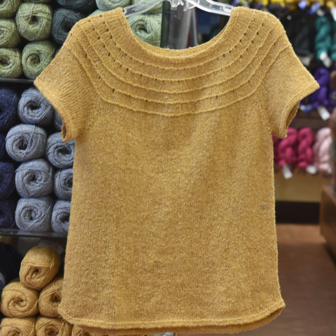 Yellow short-sleeved sweater hanging in front of wall of yarn.