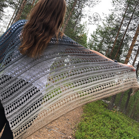 Crocheted lace shawl in a fade from blue gray to tan.