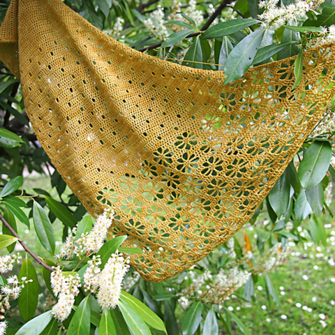 Golden yellow shawl with eyelets and floral lace hung in a green flowering tree..
