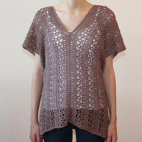 Warm tan or mauve crocheted lace top over a white tank.
