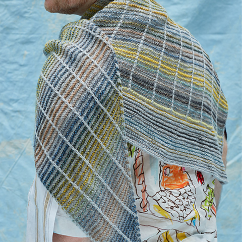 A shawl in light gray and multicolored stripes against a blue background.