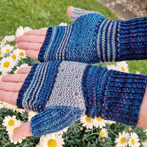 Pair of hands wearing fingerless mittens in shades of blue.