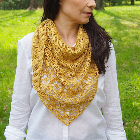 Woman wearing a golden yellow shawl with eyelets and lace around her neck over a white button down blouse.