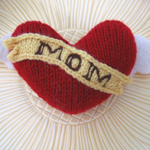 """Knit heart shape with """"Mom"""" banner and felt wings."""