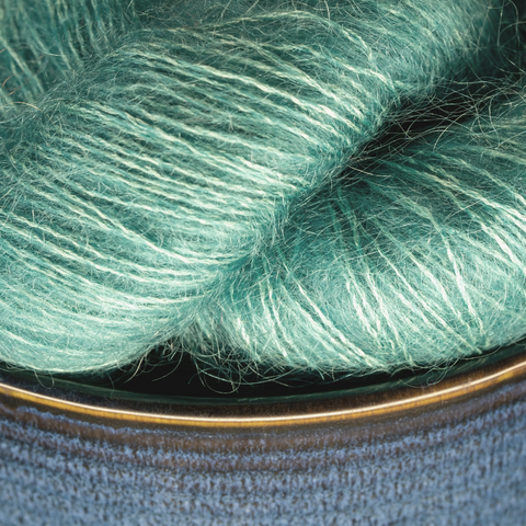 Blue ceramic bowl with well lit green lace weight yarn.