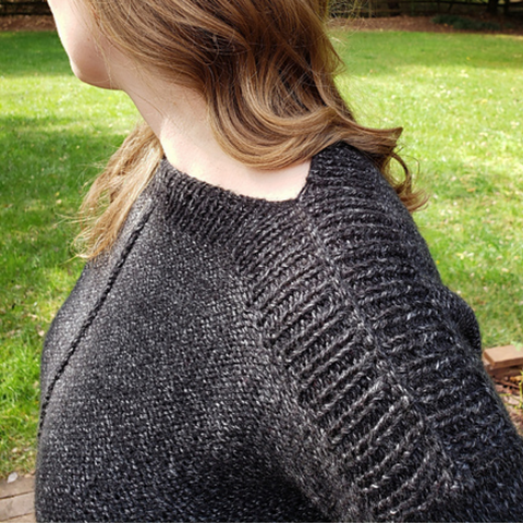 Close up of ribbing detail on the shoulder of a black heathered knit sweater.