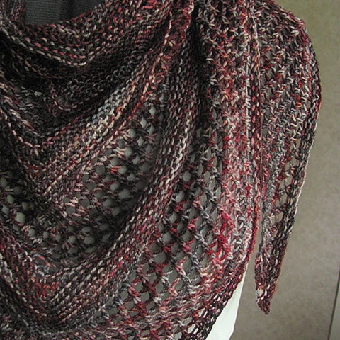 Knit lace shawl in a variegated yarn of dark purples to maroons.